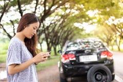 Femme asiatique à l'aide du téléphone portable tout en regardant et homme soumis à une contrainte SI photographie stock libre de droits