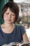 Femme asiatique affichant un magazine Photographie stock