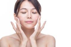 Femme asiatique appliquant la crème Image libre de droits