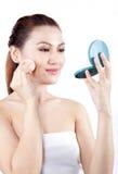 Femme asiatique appliquant la poudre sur son visage Photographie stock libre de droits