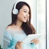 Femme asiatique appréciant la vue sur le rebord de fenêtre et écoutant la musique photo stock