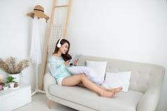 Femme asiatique appréciant se reposer sur le divan et écouter la musique photos stock