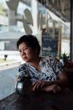 Femme asiatique attendant en café de café avec l'horloge Images libres de droits