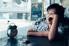 Femme asiatique attendant en café de café avec l'horloge Photo libre de droits