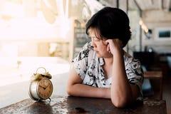 Femme asiatique attendant en café de café avec l'horloge Photographie stock libre de droits