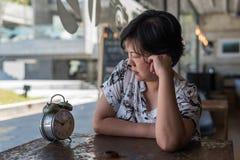 Femme asiatique attendant en café de café avec l'horloge Photos stock
