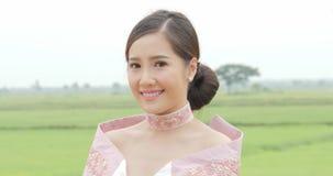 Femme asiatique attirante dans la tête de rotation de costume asiatique du sud-est traditionnel à la caméra et sourire sur un fon clips vidéos