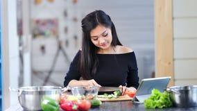 Femme asiatique attirante de tir moyen faisant cuire la salade de légume frais regardant sur l'écran du comprimé banque de vidéos