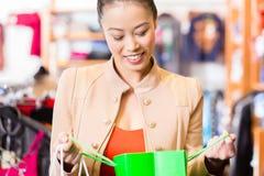 Femme asiatique avec des paniers dans la boutique Photographie stock