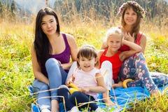 Femme asiatique avec l'enfant avec son amie caucasienne et sa fille sur un pique-nique Image stock