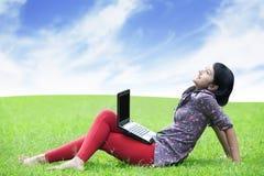 Femme asiatique avec l'ordinateur portatif extérieur Image stock