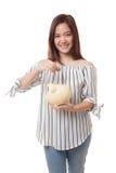 Femme asiatique avec la banque de pièce de monnaie et de pièce de monnaie de porc Photographie stock