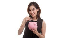Femme asiatique avec la banque de pièce de monnaie et de pièce de monnaie de porc Images libres de droits