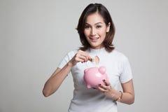 Femme asiatique avec la banque de pièce de monnaie et de pièce de monnaie de porc Image stock