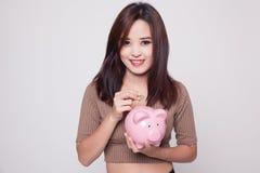 Femme asiatique avec la banque de pièce de monnaie et de pièce de monnaie de porc Photos libres de droits
