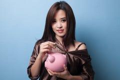 Femme asiatique avec la banque de pièce de monnaie et de pièce de monnaie de porc Images stock