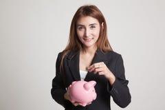 Femme asiatique avec la banque de pièce de monnaie et de pièce de monnaie de porc Photo libre de droits