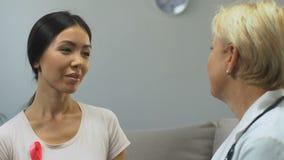 Femme asiatique avec le mammologist de visite de ruban rose, conscience de cancer du sein banque de vidéos