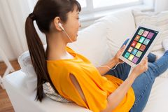Femme asiatique avec les icônes à la maison futées sur l'écran de comprimé image stock