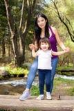 Femme asiatique avec sa petite fille dans les bois près de la rivière se tenant sur un rondin Photographie stock