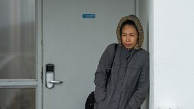 Femme asiatique bundeled dans la position de parka à côté du mur blanc photo stock