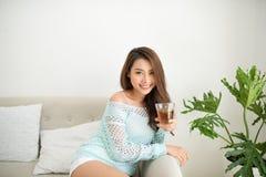 Femme asiatique buvant de son thé de matin au-dessus d'un petit déjeuner à la maison Photo stock
