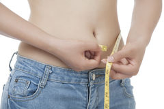 Femme asiatique convenable mesurant sa taille sur le blanc Photographie stock
