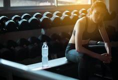 Femme asiatique convenable s'asseyant et détendre après le stage de formation dans le gymnase, femelle faisant une pause après ex images stock