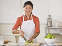 Femme asiatique coupant en tranches des pommes. Photo stock