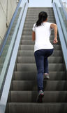 Femme asiatique courant sur des escaliers d'escalator Photos stock