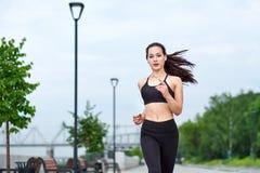 Femme asiatique courante sur le bord de mer Pulser de matin Les trains d'athlète photos stock