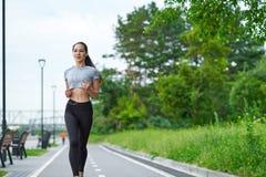 Femme asiatique courante sur le bord de mer Pulser de matin Les trains d'athlète image libre de droits