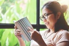 Femme asiatique décontractée lisant un livre Photographie stock libre de droits