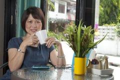 Femme asiatique détendant dans un café Images libres de droits