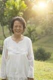 Femme asiatique d'aînés souriant à extérieur Photos stock
