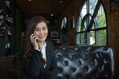 Femme asiatique d'affaires à l'aide du téléphone portable regardant l'appareil-photo photo libre de droits