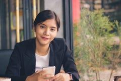 Femme asiatique d'affaires de sourire tenant le smartphone Photos stock