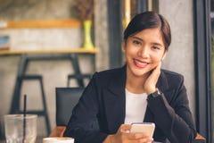 Femme asiatique d'affaires de sourire tenant le smartphone Image stock