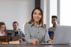 Femme asiatique d'affaires employant le groupe d'hommes d'affaires d'ordinateur portable dans l'équipe diverse centrale de course Image libre de droits