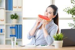 Femme asiatique d'affaires heureuse à manger la pastèque fraîche images stock