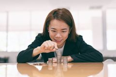 Femme asiatique d'affaires mettant la pièce de monnaie sur la pile de l'argent sur la table à l'arrière-plan intérieur de bureau photos libres de droits