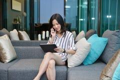 Femme asiatique d'affaires occasionnelles téléphonant et à l'aide d'un comprimé sur le sofa i image libre de droits