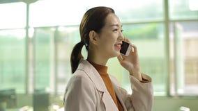Femme asiatique d'affaires parlant sur le téléphone portable banque de vidéos