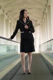 Femme asiatique d'affaires sur le passage couvert mobile Photographie stock libre de droits