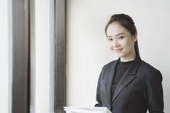 Femme asiatique d'affaires tenant des fichiers document près d'une fenêtre Images libres de droits