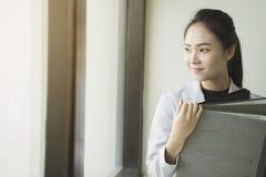 Femme asiatique d'affaires tenant des fichiers document près d'une fenêtre Image libre de droits