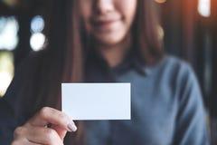 Femme asiatique d'affaires tenant et montrant la carte de visite professionnelle de visite vide dans le bureau photo stock