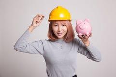 Femme asiatique d'ingénieur avec une pièce de monnaie et une banque de pièce de monnaie porcine Image libre de droits
