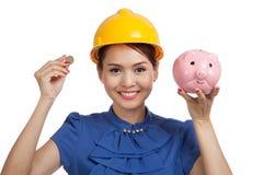 Femme asiatique d'ingénieur avec une pièce de monnaie et une banque de pièce de monnaie porcine Images libres de droits