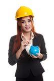 Femme asiatique d'ingénieur avec une pièce de monnaie et une banque de pièce de monnaie porcine Photos libres de droits